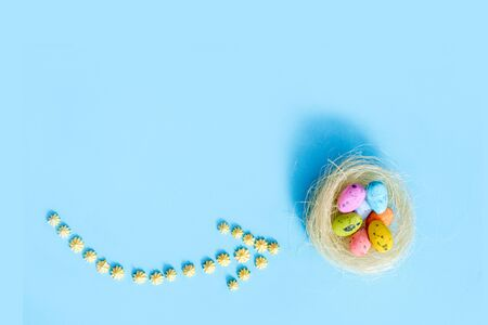 plane flies on blue background.yellow sweets. Direction sign for easter eggs. Spring and Easter are coming.Beautiful creative arrow made of colored eggs. Pointer or cursor from eggs. Top view flat