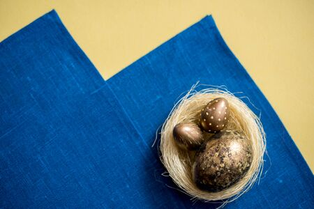 Golden easter eggs in the nest on a yellow background. blue napkin. Easter concept. copy space. Flat lay, top view, trendy modern celebration style