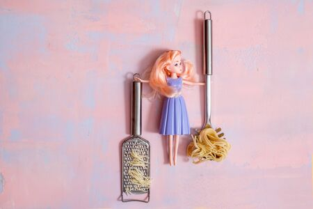 housewife cleaner. lady housewife, fashionable dress, doll fashion. The girl is cooking pasta. Copy space. Flat Lay. Top View. Zdjęcie Seryjne