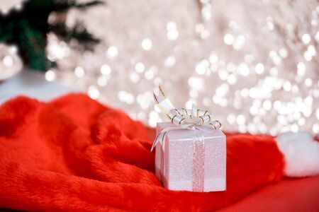 Christmas white gift box with a large bow standing on red hat santa calus against a background bokeh of twinkling golden bokeh lights. New Year's gift. Copy space.
