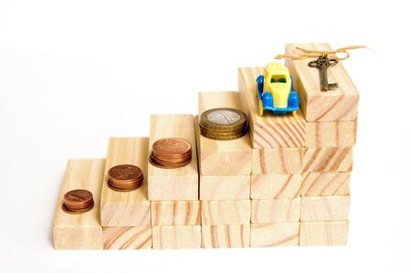 Wooden blocks step up. Money, a house key and a car.