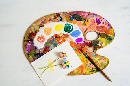 wooden art palette with paint and brushes on white.LGBT concept. lesbian gay , bisexual transsexual. Banco de Imagens