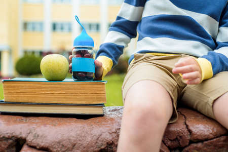 Lunch time at school.A boy in the schoolyard eats fresh fruits and vegetables. change of outdoors Archivio Fotografico