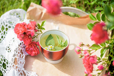 tea with petals of roses on a knitted cloth, romance, love.Summer in the village, natural tea, breakfast outdoors.