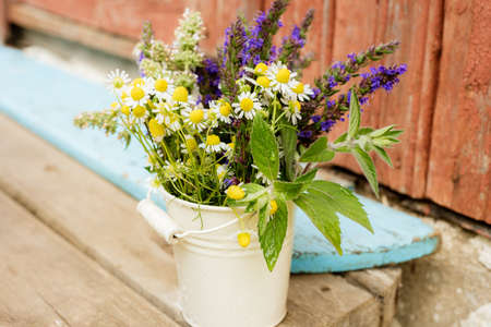 Bouquet of tea flowers. Chamomile, lemon balm and mint. Healthy diet. morning in the village. wooden background