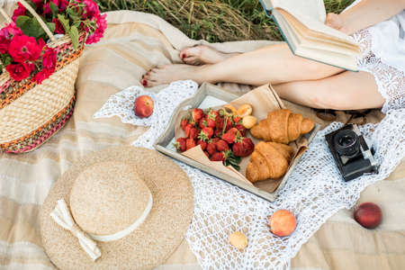 A girl reads a book, next to a hat, croissants, bread and fruits, fresh flowers in a basket, strawberries. Beautiful summer in the village. picnic outdoors, relaxing on holiday