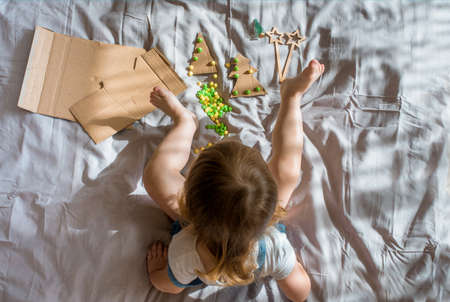 A child carves a Christmas tree from cardboard. Christmas decoration, hand made and Zero waste. child makes crafts on the bed at home. Div. Flat lay, top view