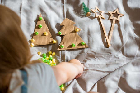 A child carves a Christmas tree from cardboard. Christmas decoration, hand made and Zero waste. child makes crafts on the bed at home. Div. top view