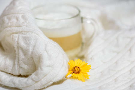 Autumn or winter cozy composition. Cup of coffee, warm knitted White sweater. Flat lay, top view