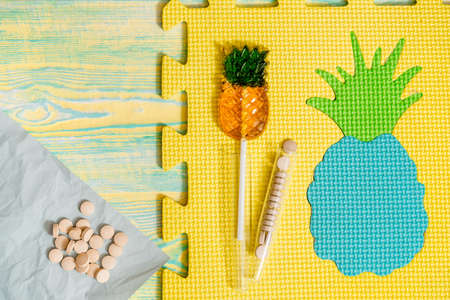 Natural plant-based diet pills, pineapple capsules. Bright pineapple candy on a gray background, crumpled paper. The concept of homeopathic medicine. Vitamins in fruits. Vitamins in fruits
