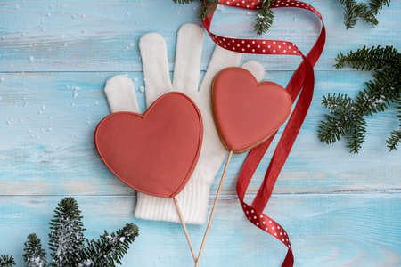 Christmas gingerbread on a white mitten. on a blue wooden background. New Year card. Red heart on a stick. sweet candy.