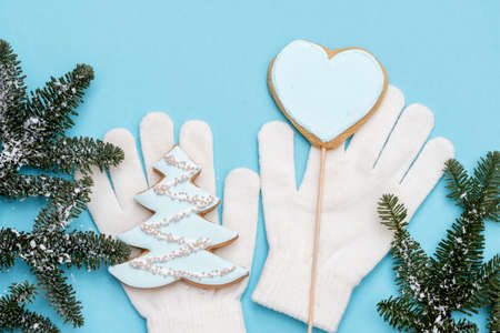 Christmas gingerbread on a white mitten. on a blue wooden background. Christmas tree with balls and a house. New Year card