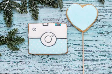 Christmas gingerbread camera on a blue wooden background. Christmas tree with balls and a house. New Year card Archivio Fotografico