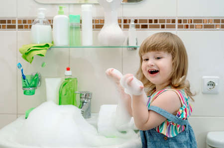 Funny little baby girl with curly hair playing with foam in bath.A lot of foam in a white washbasin. Cleaning the bathroom, playing with water at home