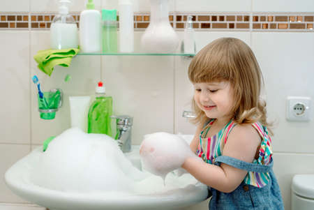 bath foam baby.Cleaning the bathroom. Foam in the washbasin, green soap and green gloves in the girl. Clean house. cleaning up. child washes plumbing.