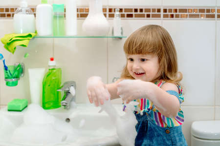 bath foam baby.Cleaning the bathroom. Foam in the washbasin, green soap,green gloves in the girl. Clean house. cleaning up. child washes plumbing.Wet clothes Stok Fotoğraf