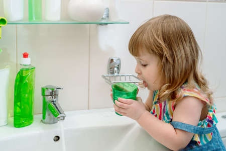 Morning hygiene in the bathroom. Baby the girl washes, brushes her teeth, rinses her mouth with water, and wipes herself with a towel. Smiling young girl brushing teeth and holding glass of water