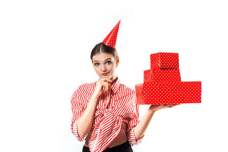 Party or birthday. Emotional beautiful girl in red with big gift boxes. Isolate on white in the studio. Surprise and joy, laughs and screams