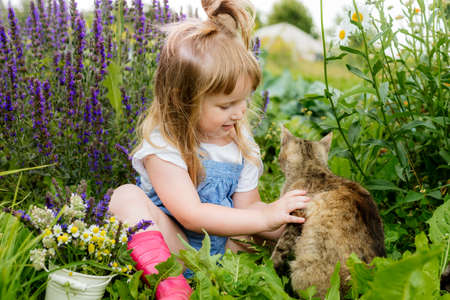 Happy little child with cat. Girl playing with pet outdoors on the garden. Summer nature