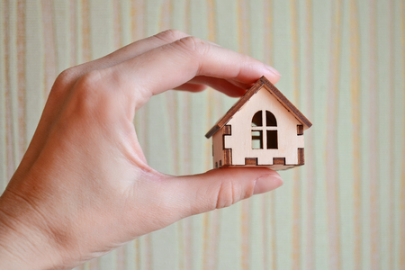 Wooden toy house model in woman's hand on light striped background, front view