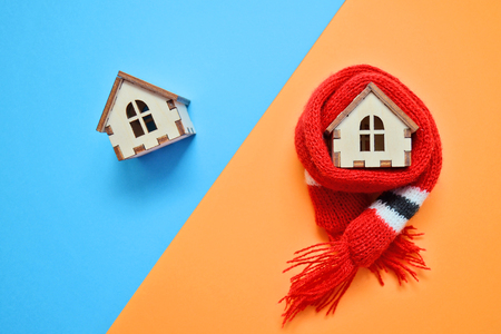 Dwa drewniane domy z zabawkami na niebieskim i pomarańczowym tle, jeden dom ubrany na szaliku, koncepcja domów izolacyjnych z copyspace, podzielony po przekątnej, zimny i ciepły dom Zdjęcie Seryjne