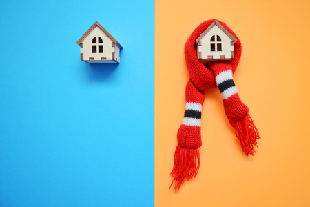 Two wooden toy houses on blue and orange background, one house weared on scarf, concept for insulation houses with copyspace, cold and warm house