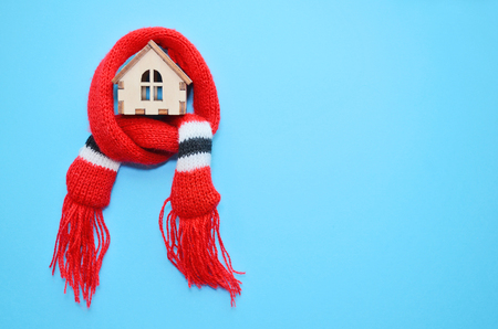 Wooden toy house with windows in a red scarf on blue background, warm house, insulation of house, copyspace Stock Photo