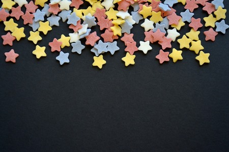 A lot of sugar colored stars on top of black background macro, background for confectioners with copyspace. 写真素材