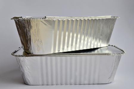 Two disposable foil food containers for takeaway on a white background