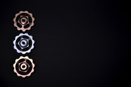 Color rollers, silver gears for bicycle rear derailleur on black background in left side, with a copyspace Banque d'images