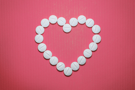 Lots of white smooth convex tablets with dividing strip on pink striped background, in the form of heart, top view 版權商用圖片