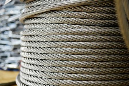 Sauberes neues Stahlseil, Stahldraht oder Stahlseil, aufgewickelt auf einer im Regal stehenden Spule