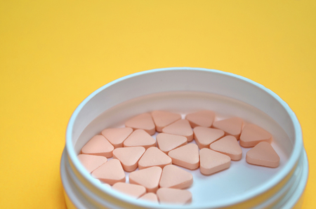 Pink triangular unusual pills in a white round box on a yellow background with space for text, side view