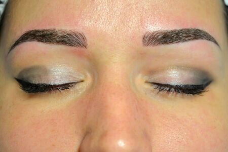The finished result of microblading, dark eyebrows, permanent makeup on eyebrows. Фото со стока