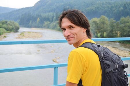 White man tourist in a yellow t-shirt with a backpack stands on a bridge over a mountain river in the background of the Carpathian mountains