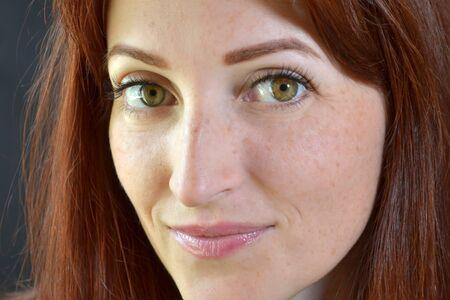 Weißes Mädchen mit roten Haaren und grünen Augen mit Wimpernverlängerung auf dunklem Hintergrund sieht schlau und emotional aus Standard-Bild