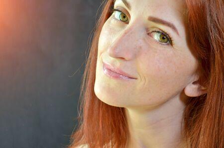 Chica blanca con cabello rojo y ojos verdes con extensiones de pestañas sobre fondo oscuro mirando hacia adelante con brillo, con copyspace