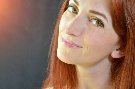 White girl with red hair and green eyes with eyelash extensions on dark background looking forward with glow, with copyspace