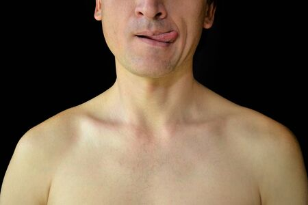 White mens bare chest and half of the face on a black background. A man playfully shows his tongue