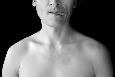 White mens bare chest and half of the face on a black background. A man playfully shows his tongue. Photo in black and white