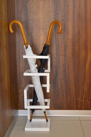 Black and white umbrella stand in a special geometric stand against the wooden wall in the room, vertycally oriented