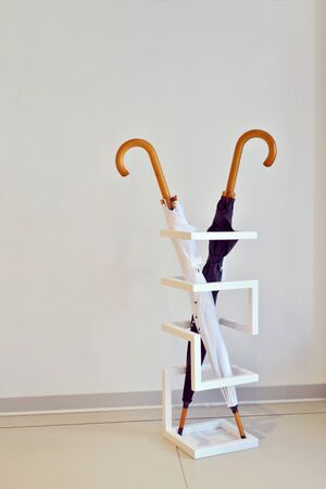 Black and white umbrella stand in a special geometric stand against the white wall in the room, vertycally oriented