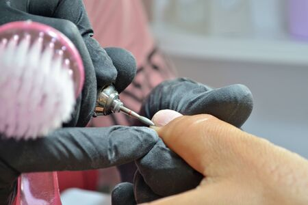 Master of manicure in black gloves and with brush makes hardware manicure by nail cutter, closeup