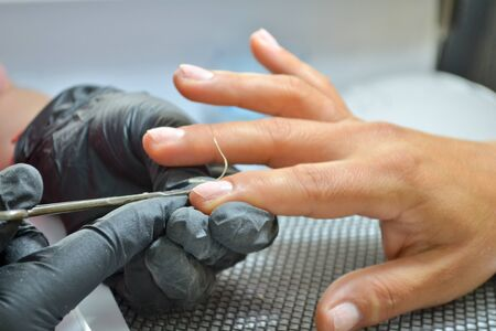 Manicurist in black gloves makes a cut manicure, trimming the cuticle on finger with scissors