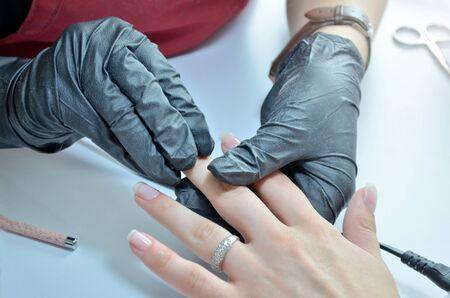 Manicurist in black gloves rubs a varnished nail Banque d'images