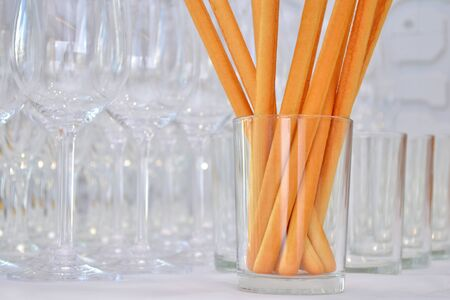 Breadsticks stand in a clear glass at a party, behind are empty glasses