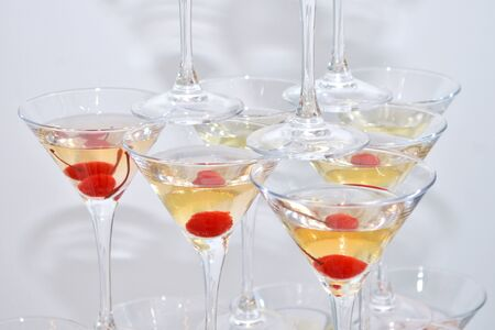 Triangular martini glasses, filled with champagne with cherries and liquid nitrogen, creating steam, built in the shape of a pyramid