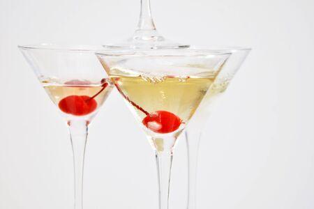 Copas de martini triangulares, llenas de champán con cerezas y nitrógeno líquido, creando vapor, construidas en forma de pirámide.