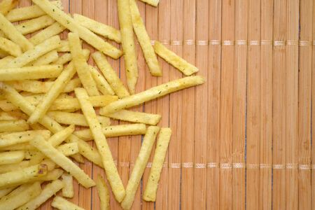 Snack french fries. Fried potatoes are poured out of the package on a wooden mat with copyspace Фото со стока