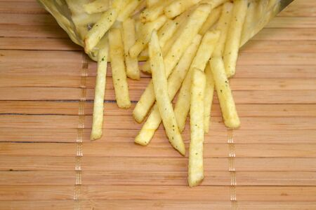 Snack french fries in foil pack. Fried potatoes are poured out of the package on a wooden mat with copyspace